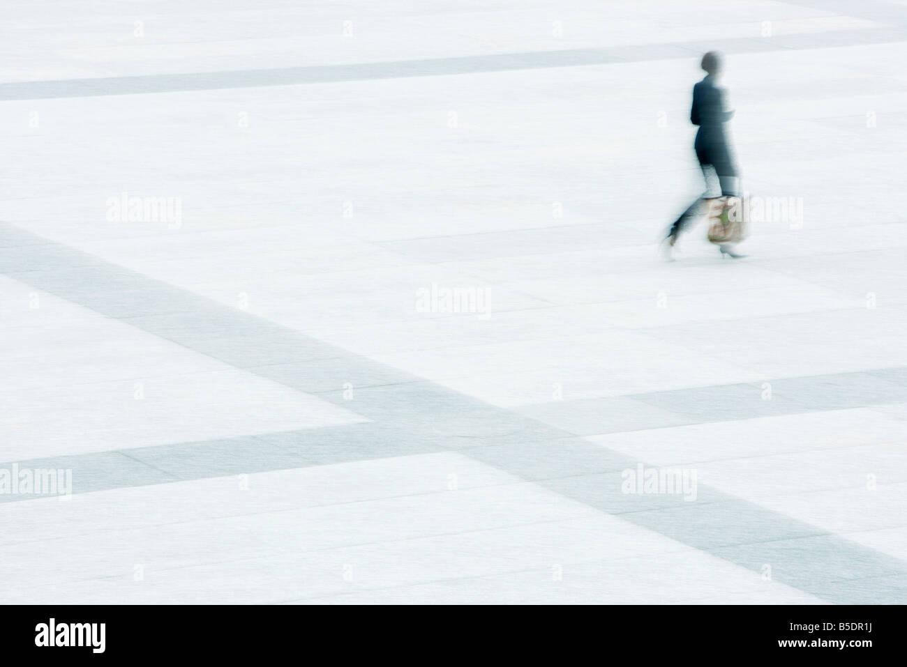 Donna attraversando a piedi piazza Foto Stock