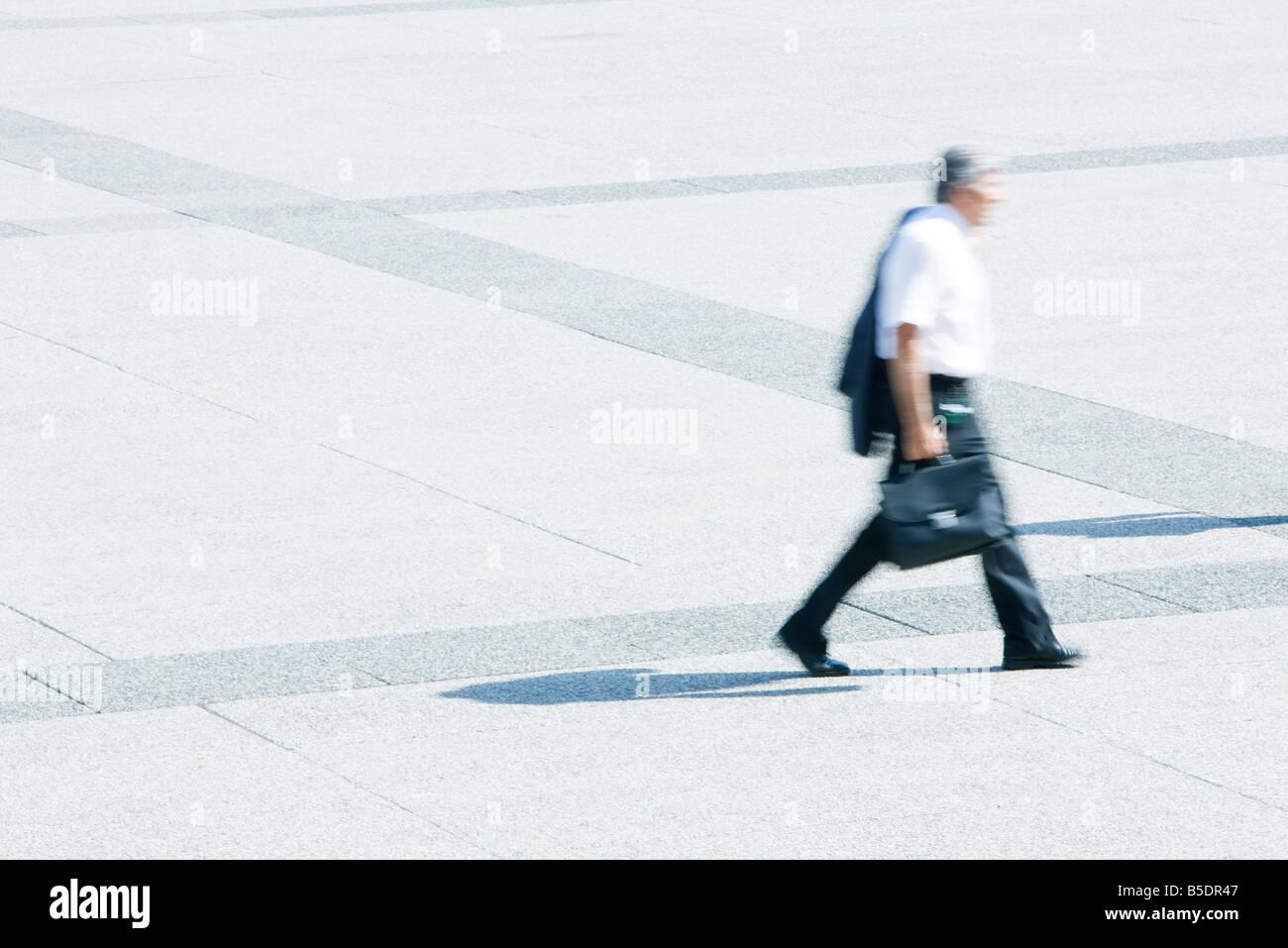 Imprenditore con camicia sulla spalla attraversando a piedi piazza Foto Stock