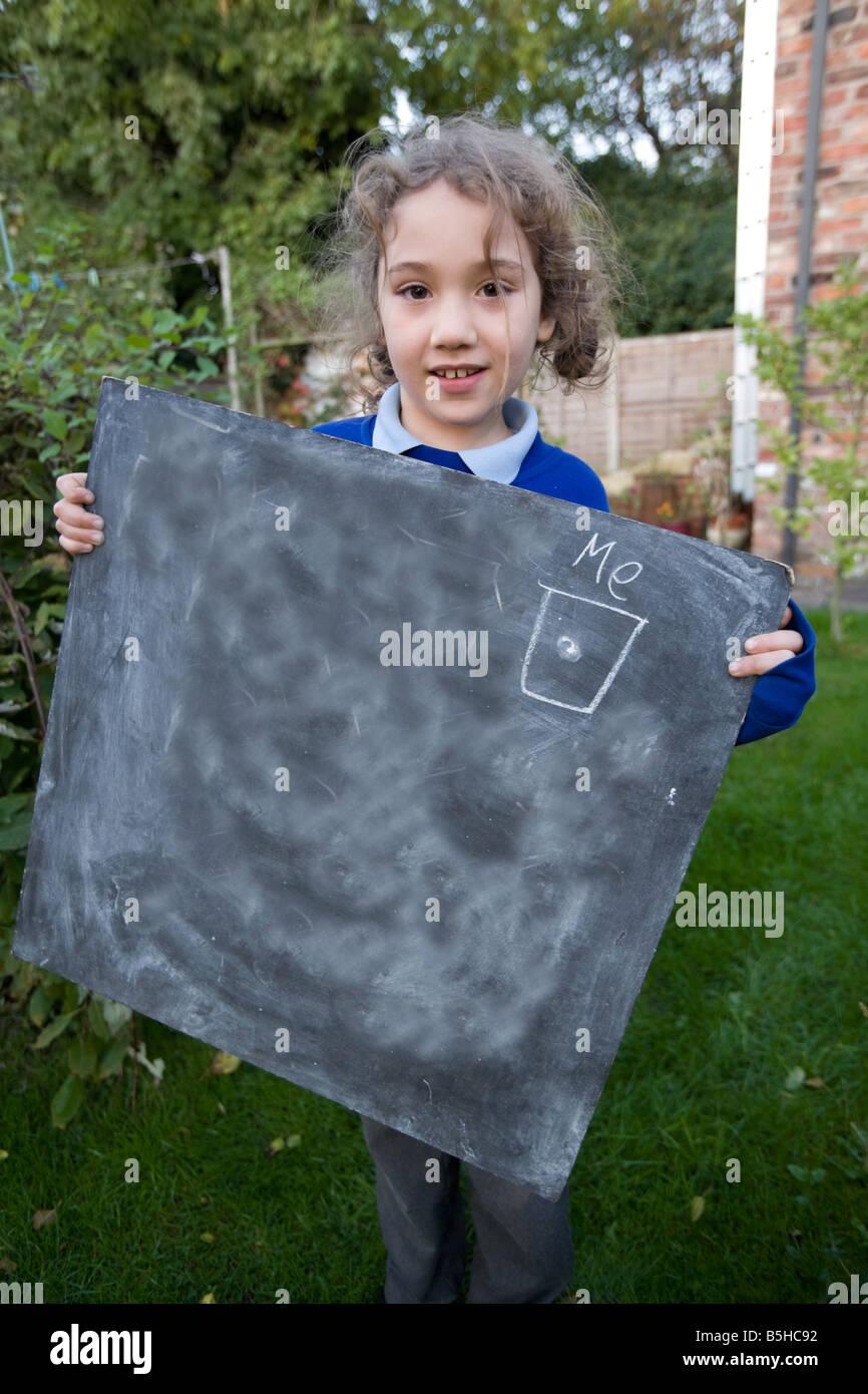 Una scuola primaria bambino mostra azienda blank chalk board Immagini Stock