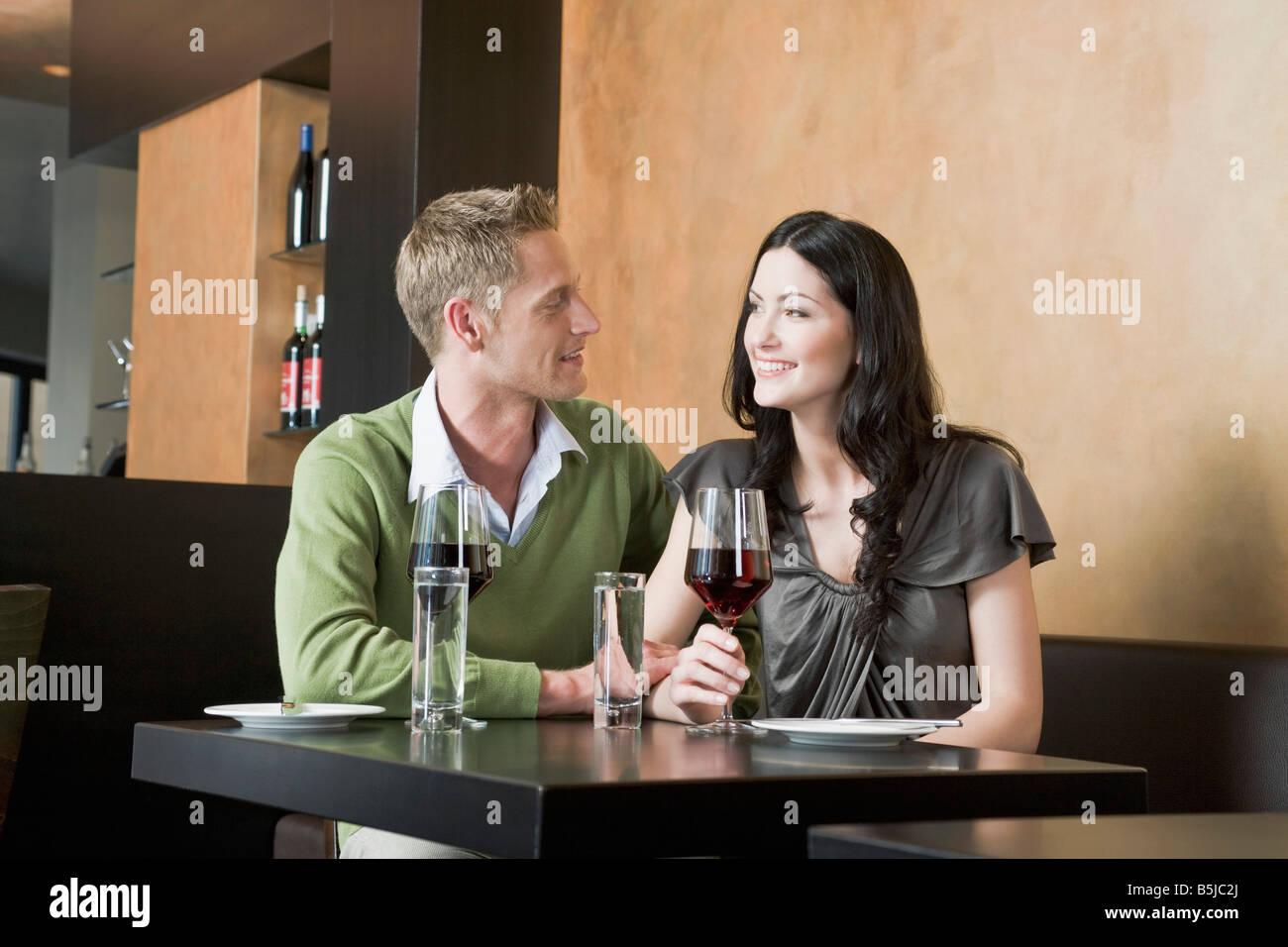 Coppia giovane seduti al ristorante con i bicchieri di vino rosso Immagini Stock