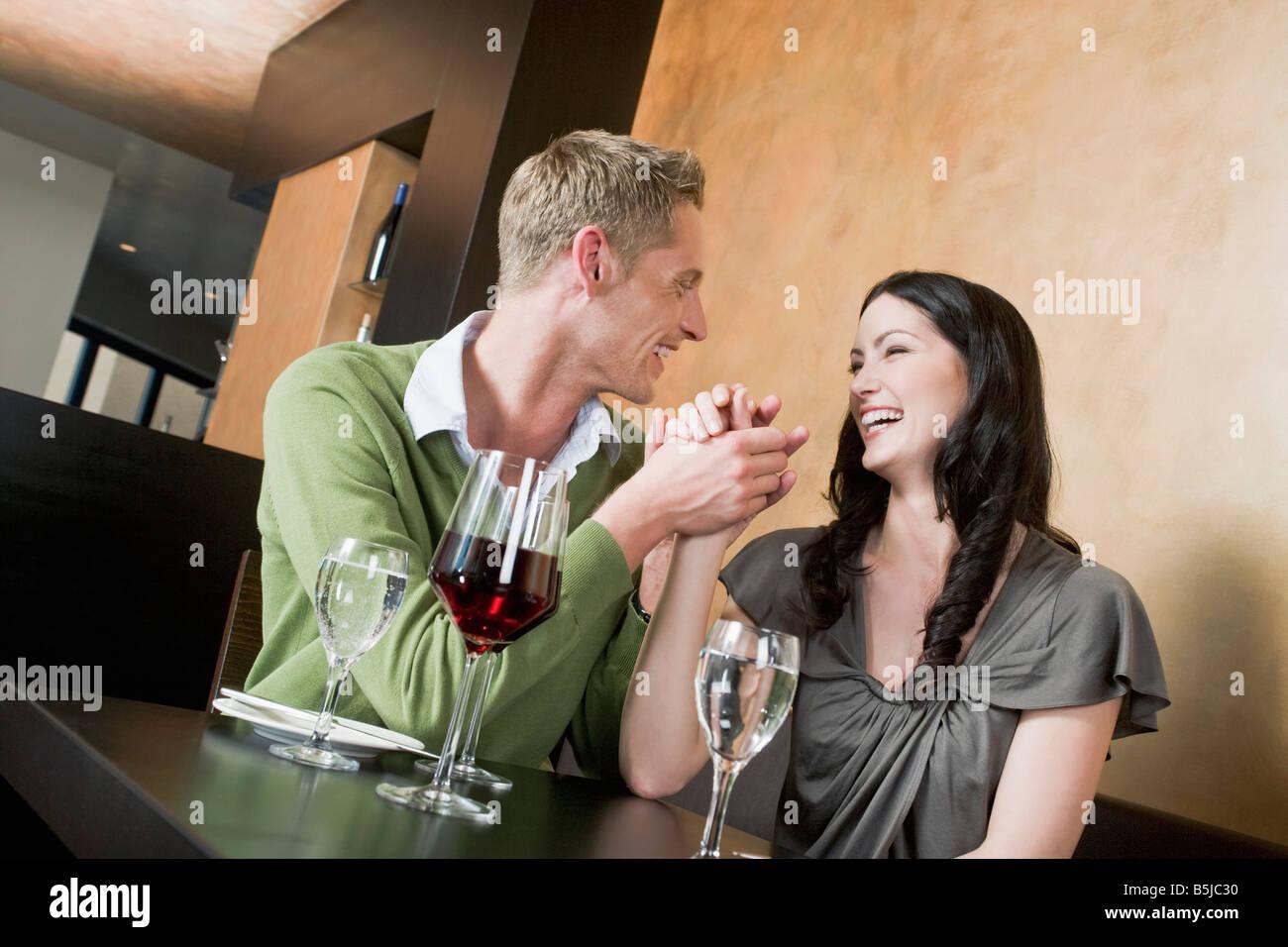 Coppia giovane al ristorante tenendo le mani Immagini Stock