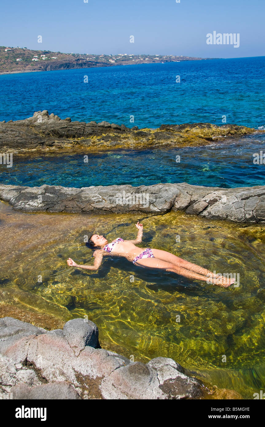 Donna galleggiante nella colorata piscina di acqua di mare for Isola gonfiabile piscina