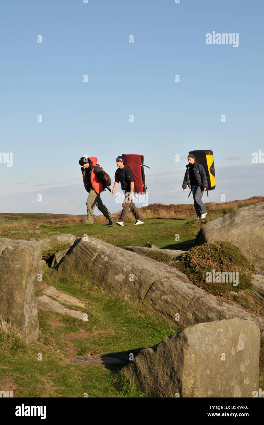 Tre giovani uomini che trasportano crash pad camminando sul bordo Froggatt nel distretto di Peak Derbyshire Inghilterra Foto Stock