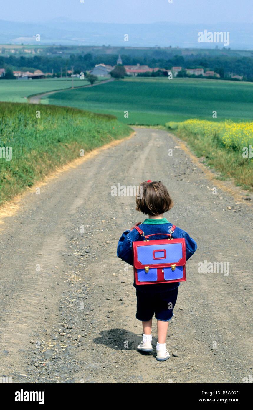 Poco ragazza camminare lungo una strada di campagna che va alla scuola del villaggio di campagna Immagini Stock