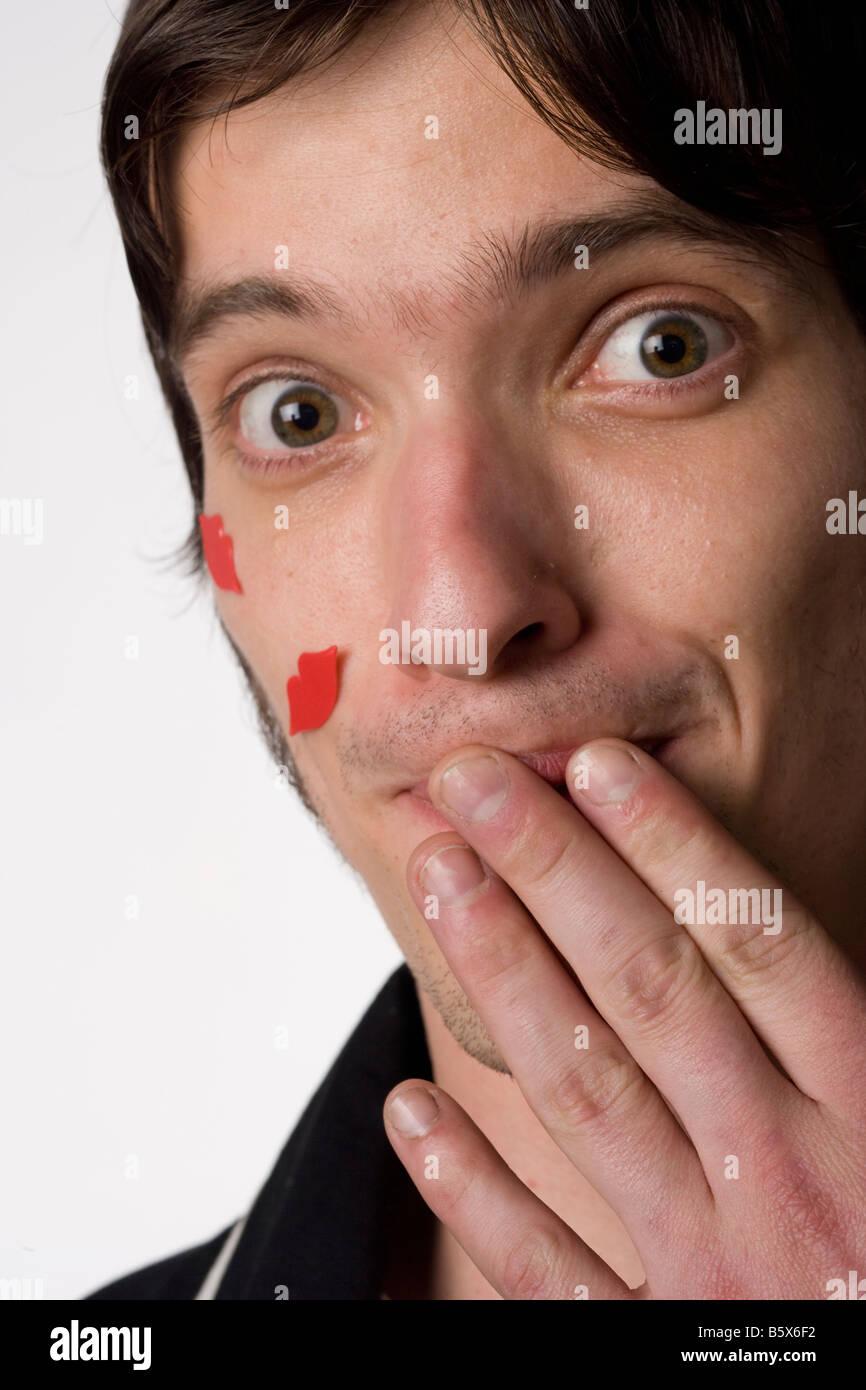 Ritratto di un giovane uomo su uno sfondo bianco con novità baci sul suo volto Immagini Stock