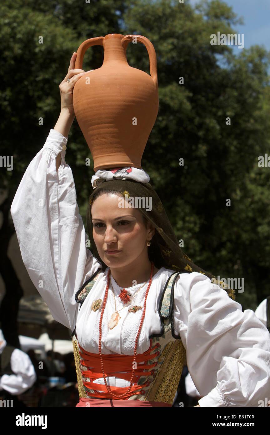 Giovane donna che indossa il costume tradizionale che trasportano un anfora  sul suo capo alla cavalcata sarda festival di Sassari be7c2008c54