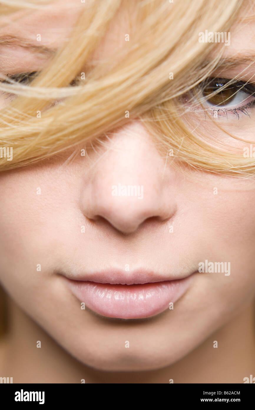Giovane donna bionda, capelli che copre parzialmente il suo viso, trattamenti per il viso di close-up Immagini Stock