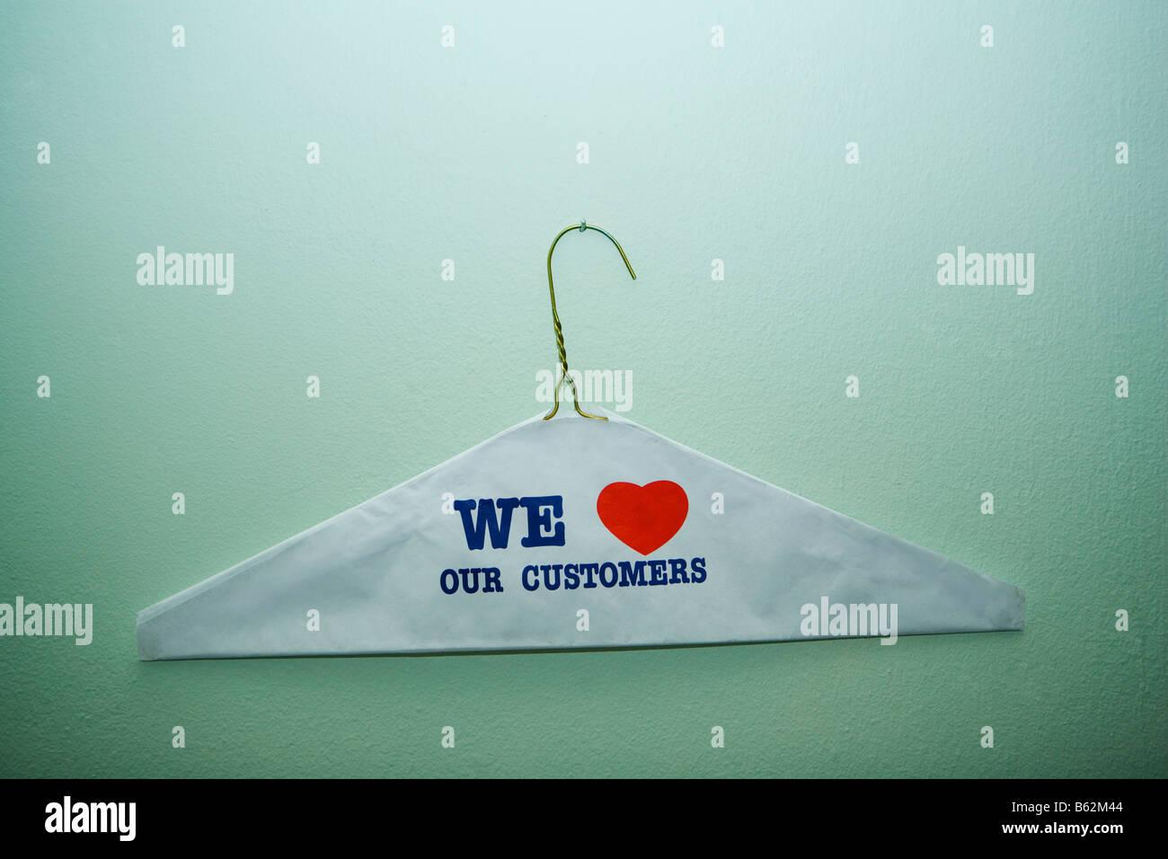 Close-up del testo che dobbiamo amare il nostro cliente dipinta su un panno su un appendiabiti, New York City, nello Immagini Stock