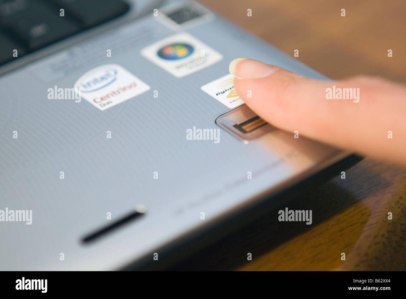 La donna accede a un PC notebook scorrendo il dito su un lettore di impronte digitali biometrico. Immagini Stock