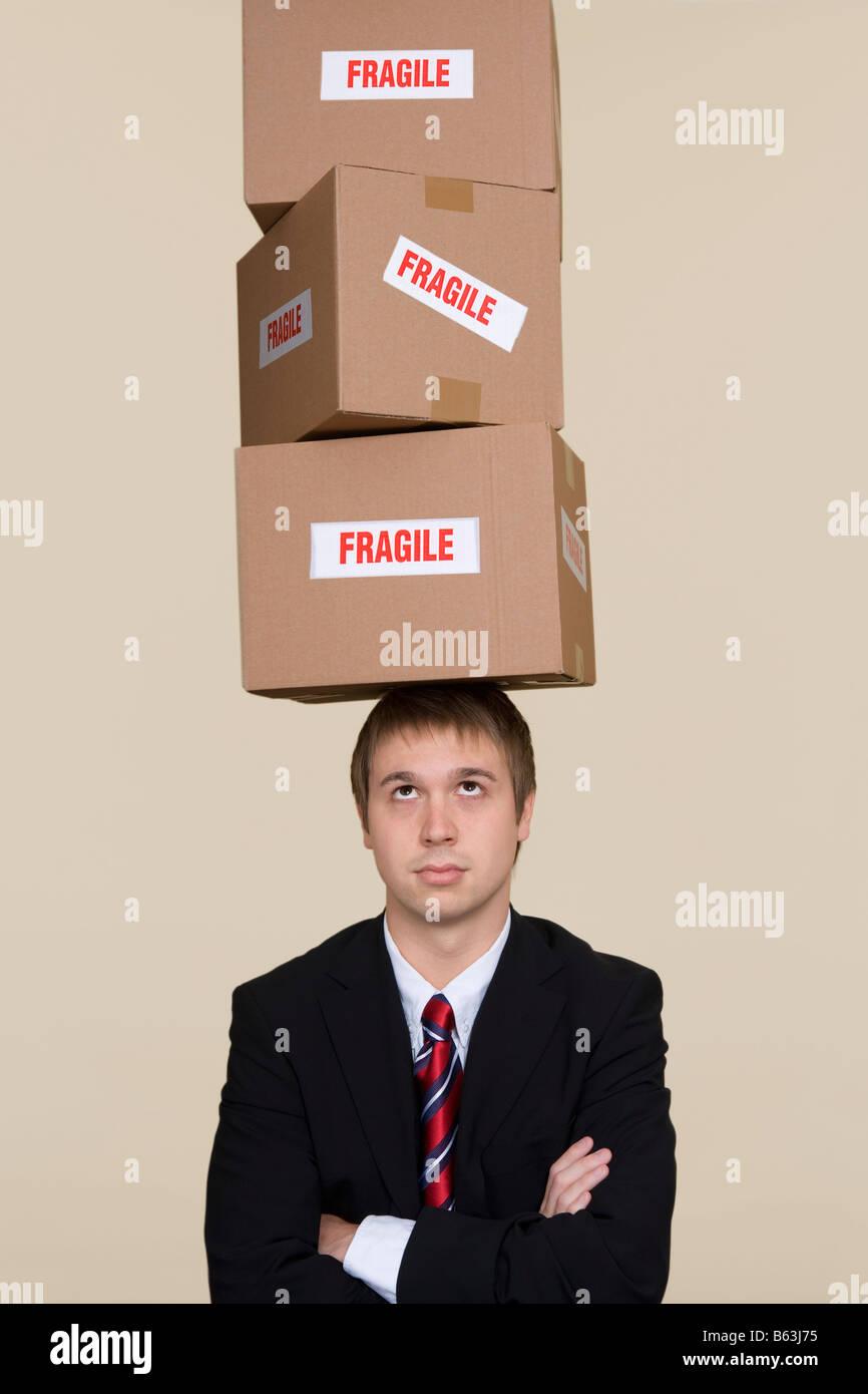 Giovane imprenditore scatole di bilanciamento sulla testa Immagini Stock