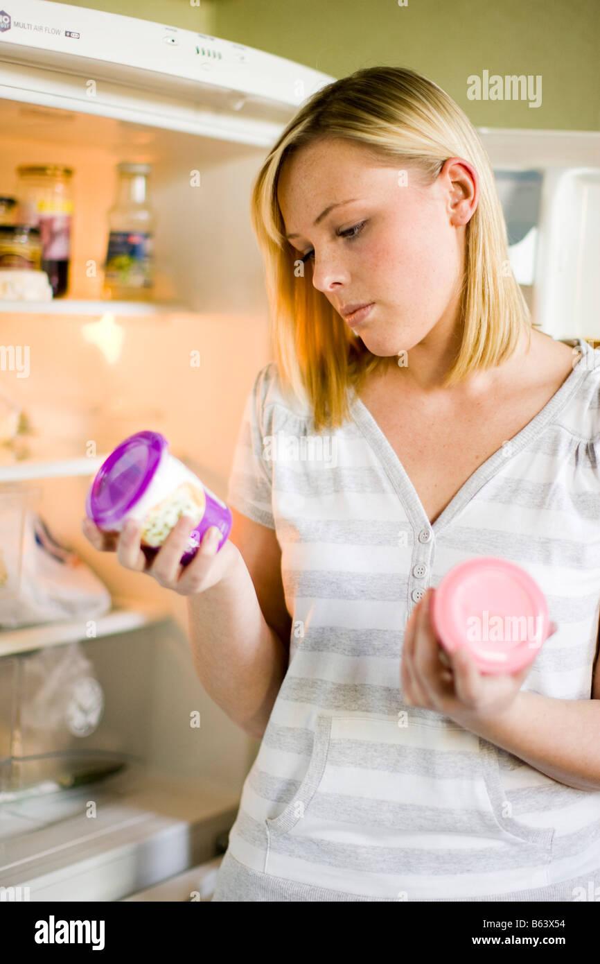 Donna che guarda il cibo in frigo Immagini Stock