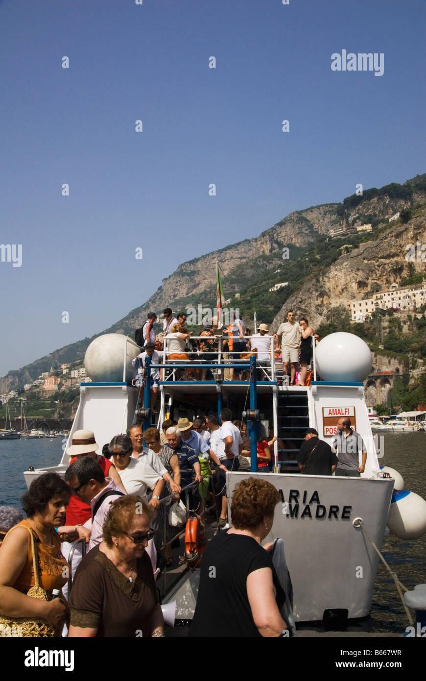 Un gruppo di cittadini anziani partono un traghetto attraccato in Amalfi, Campania, Italia Immagini Stock