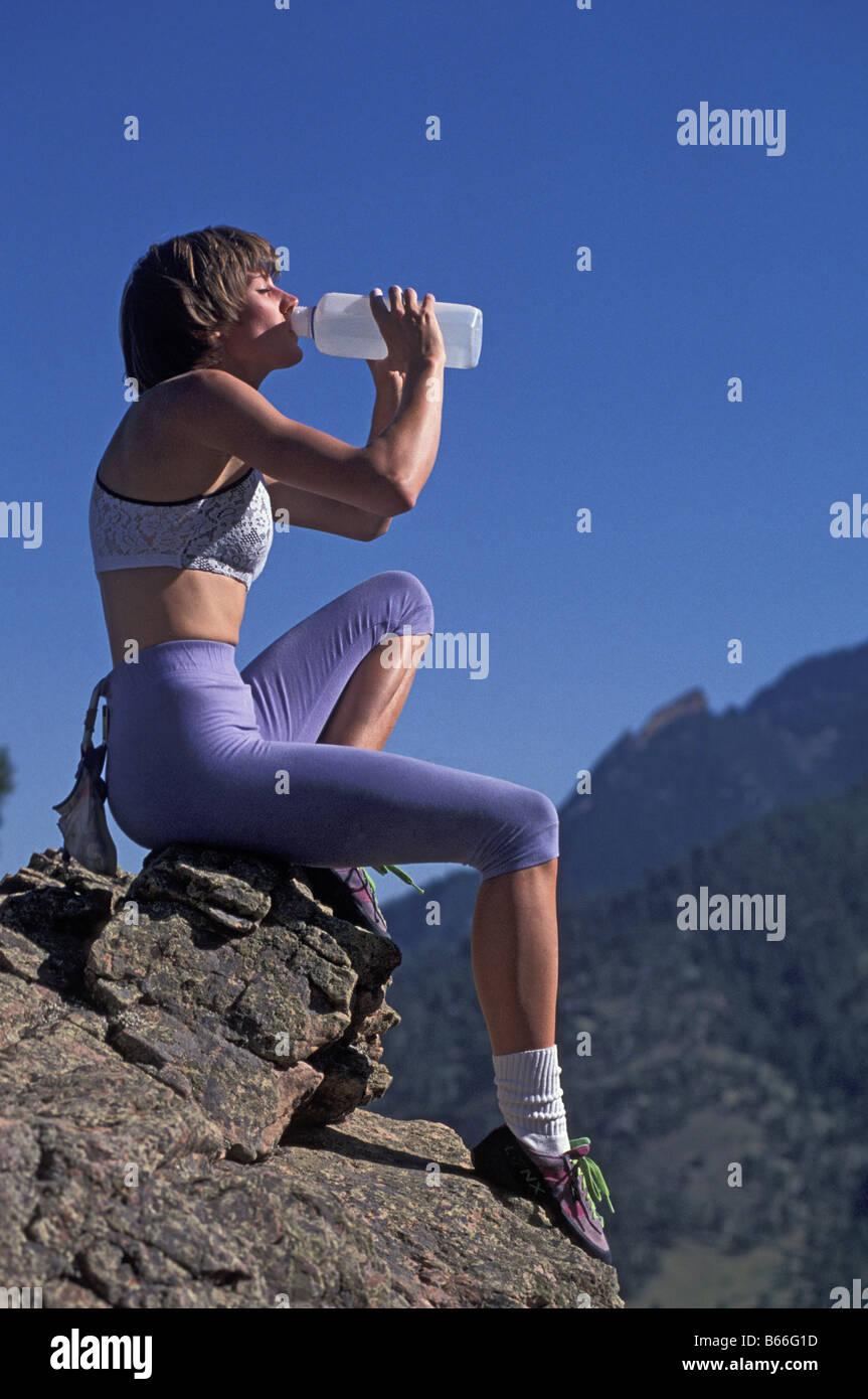 Donna rocciatore bere durante una pausa di riposo Immagini Stock