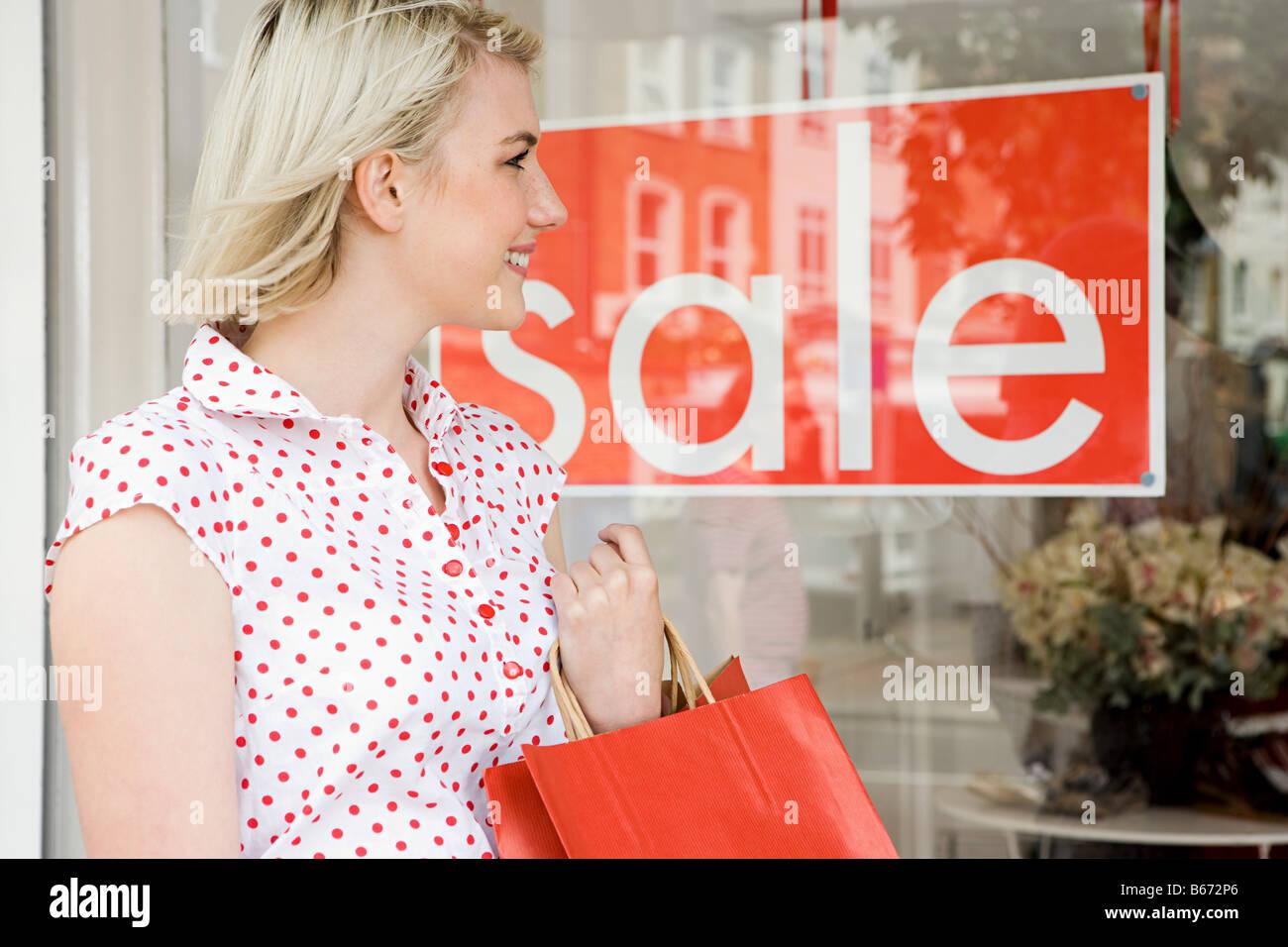 Donna che guarda un negozio vendita Immagini Stock