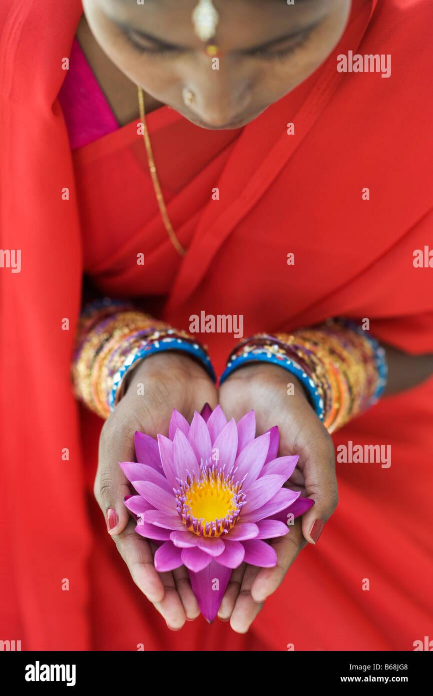 Donna indiana offre un Nymphaea ninfea tropicale fiore nella sua mani a tazza. Andhra Pradesh, India Foto Stock