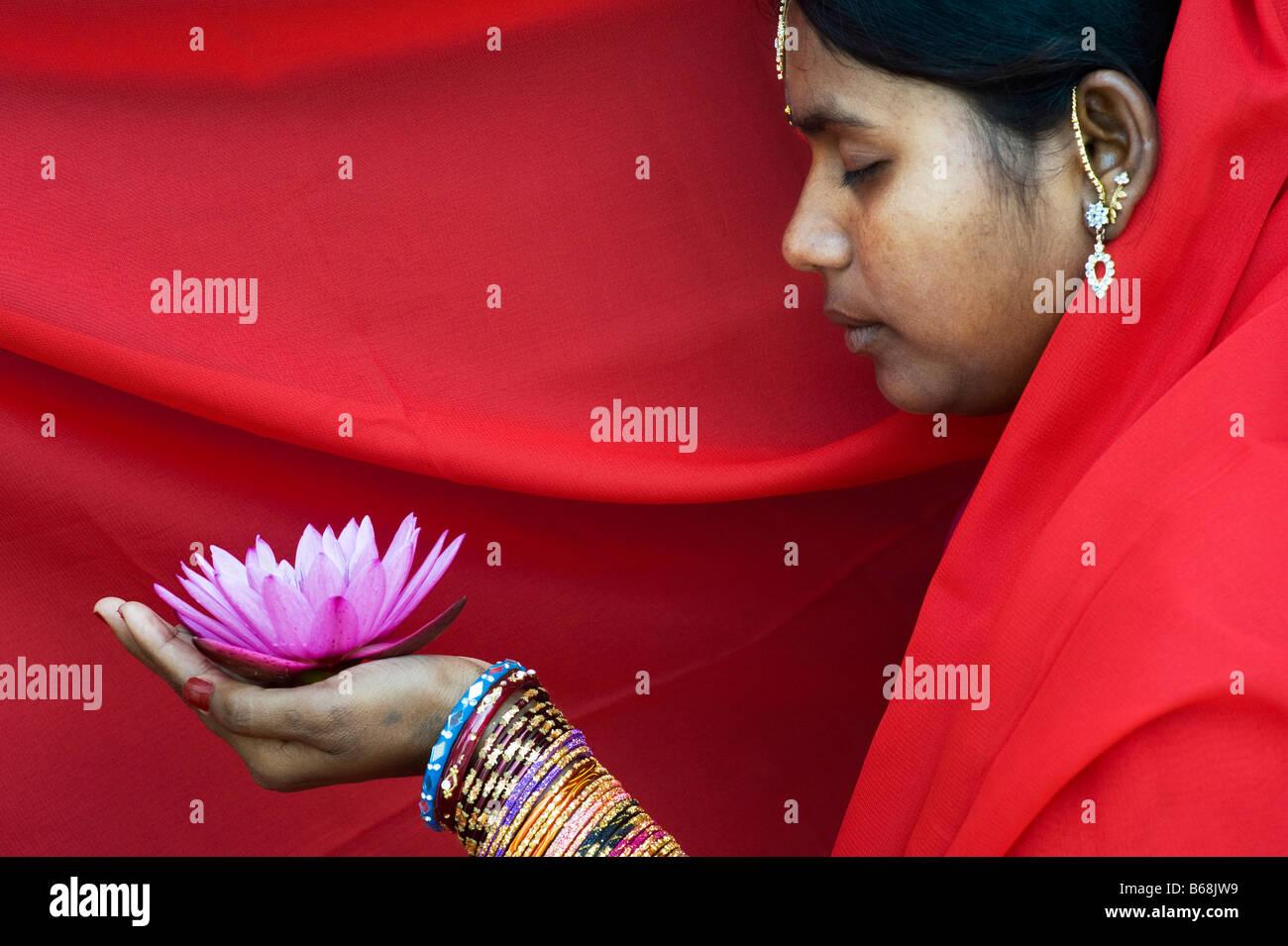 Donna indiana offre un Nymphaea ninfea tropicale fiore in un sari rosso Foto Stock