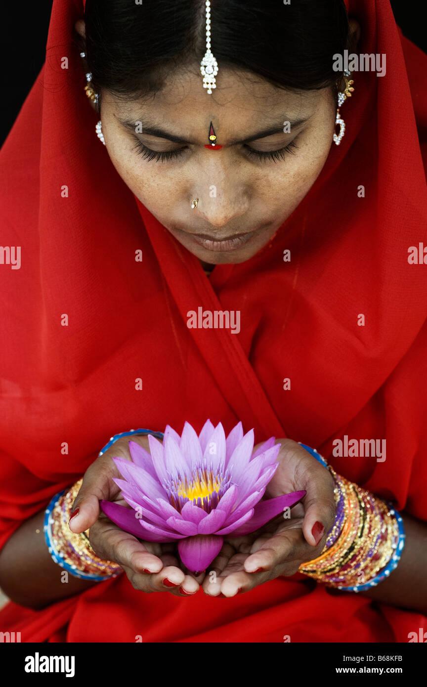 Donna indiana offre un Nymphaea ninfea tropicale fiore in un sari rosso. Andhra Pradesh, India Immagini Stock