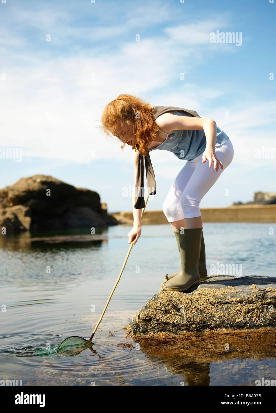 Ragazza giovane con attività di pesca in rock pool Immagini Stock