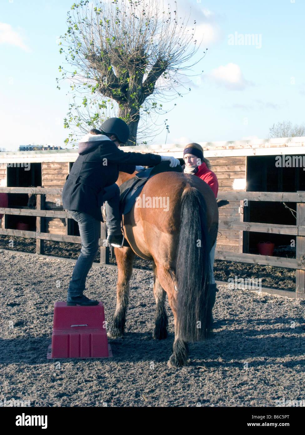 Un istruttore della Scuola di insegnamento ai bambini di guidare in una scuola di equitazione di Londra, Regno Unito. Immagini Stock