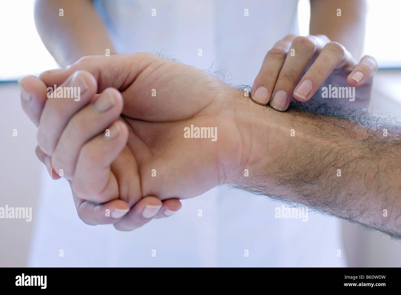 Controllo dell impulso. L'infermiera utilizzando le dita per sentire un polso. Immagini Stock