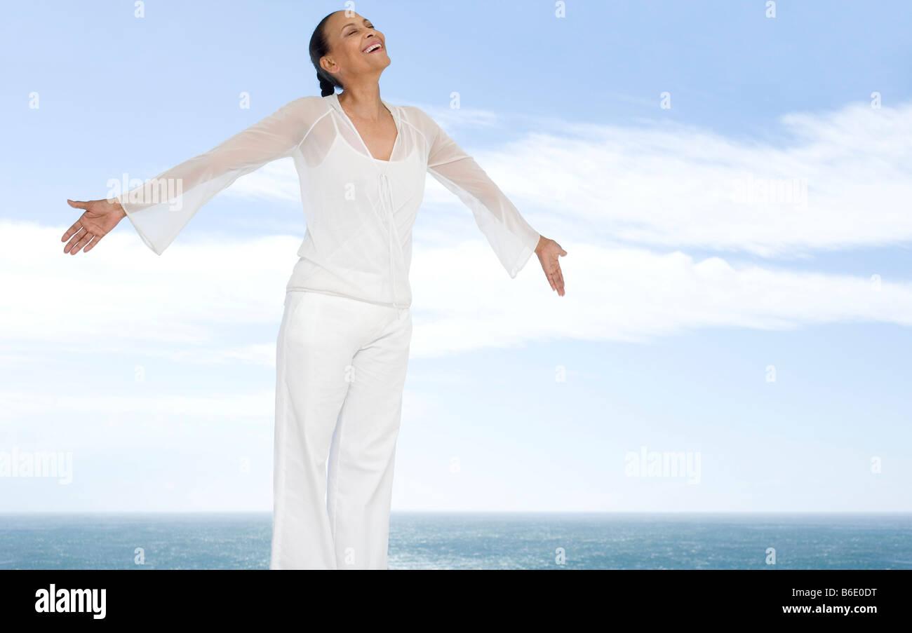 Donna felice con le braccia aperte accanto al mare. Immagini Stock