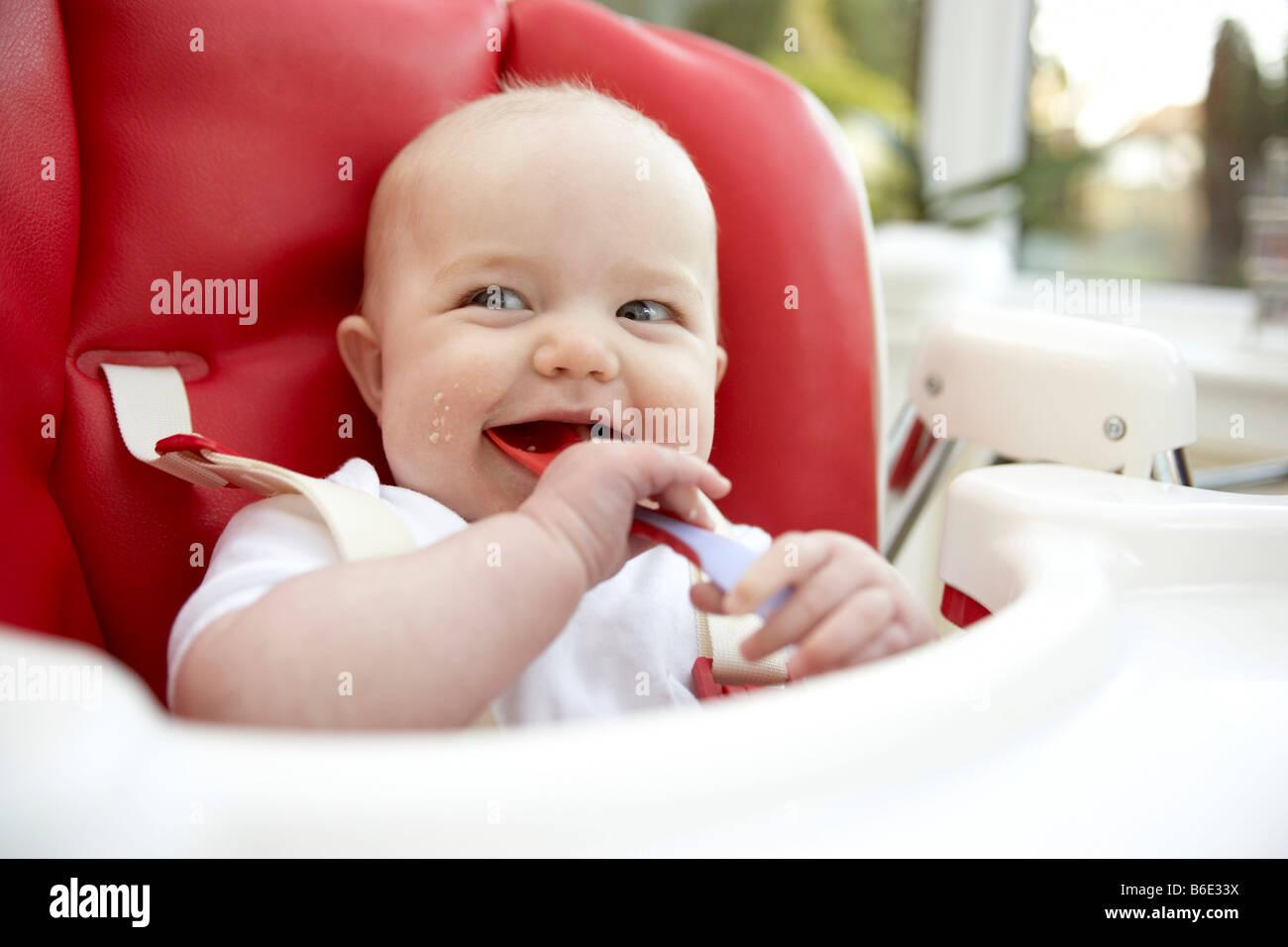 Baby girl (6-11 mesi)a mangiare da un cucchiaio Immagini Stock