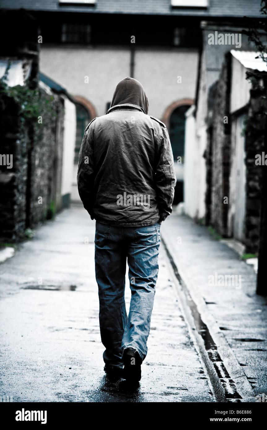 Giovane uomo che indossa una giacca con cappuccio solo e isolato a piedi giù un vicolo in una città UK Immagini Stock