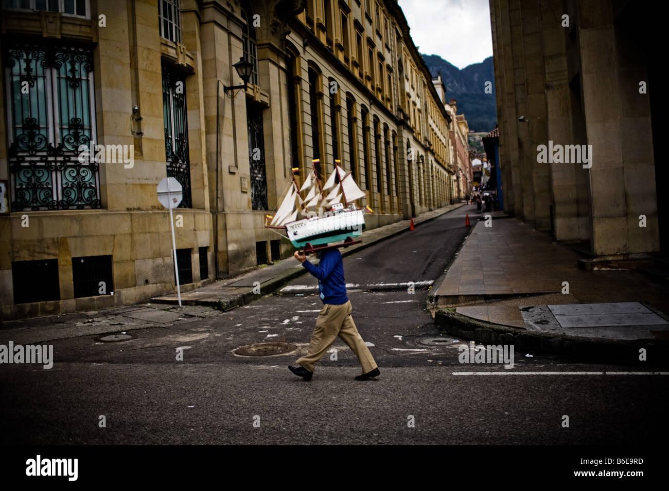 Un uomo porta un modello di barca a vela in fondo a una strada a Bogotà, in Colombia. Immagini Stock