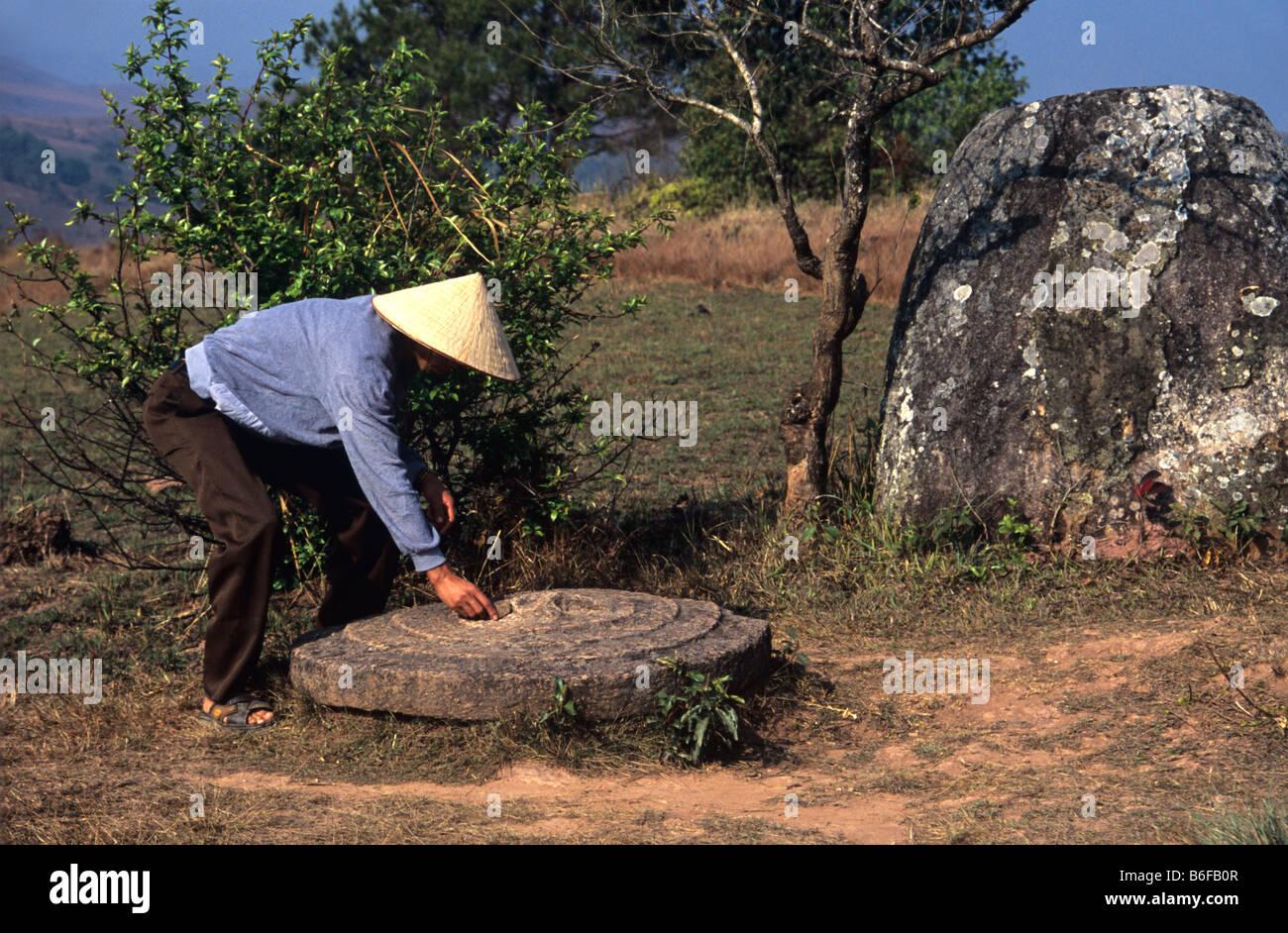 Un laotiano abitante con il coperchio scolpito di un gigante di pietra jar sulla pianura di vasi (sito 2), Phonsavan, Foto Stock