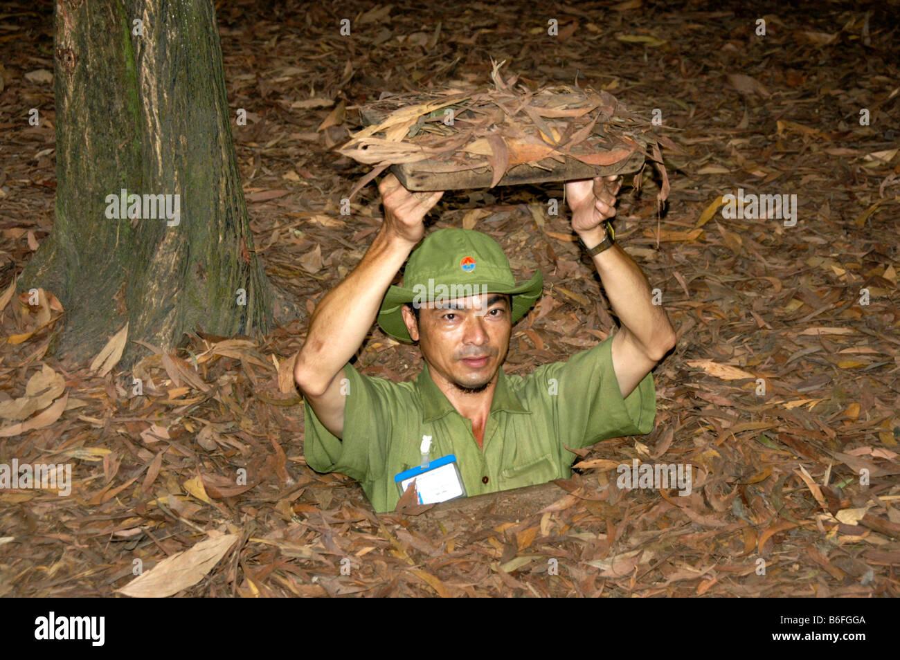 Uomo in una grotta in terra, Cu Chi, Vietnam, sud-est asiatico Immagini Stock