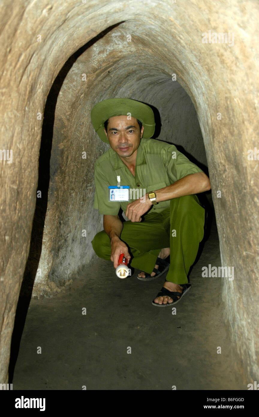 L'uomo accovacciato in un basso corridoio di una grotta, Cu Chi, Vietnam, sud-est asiatico Immagini Stock