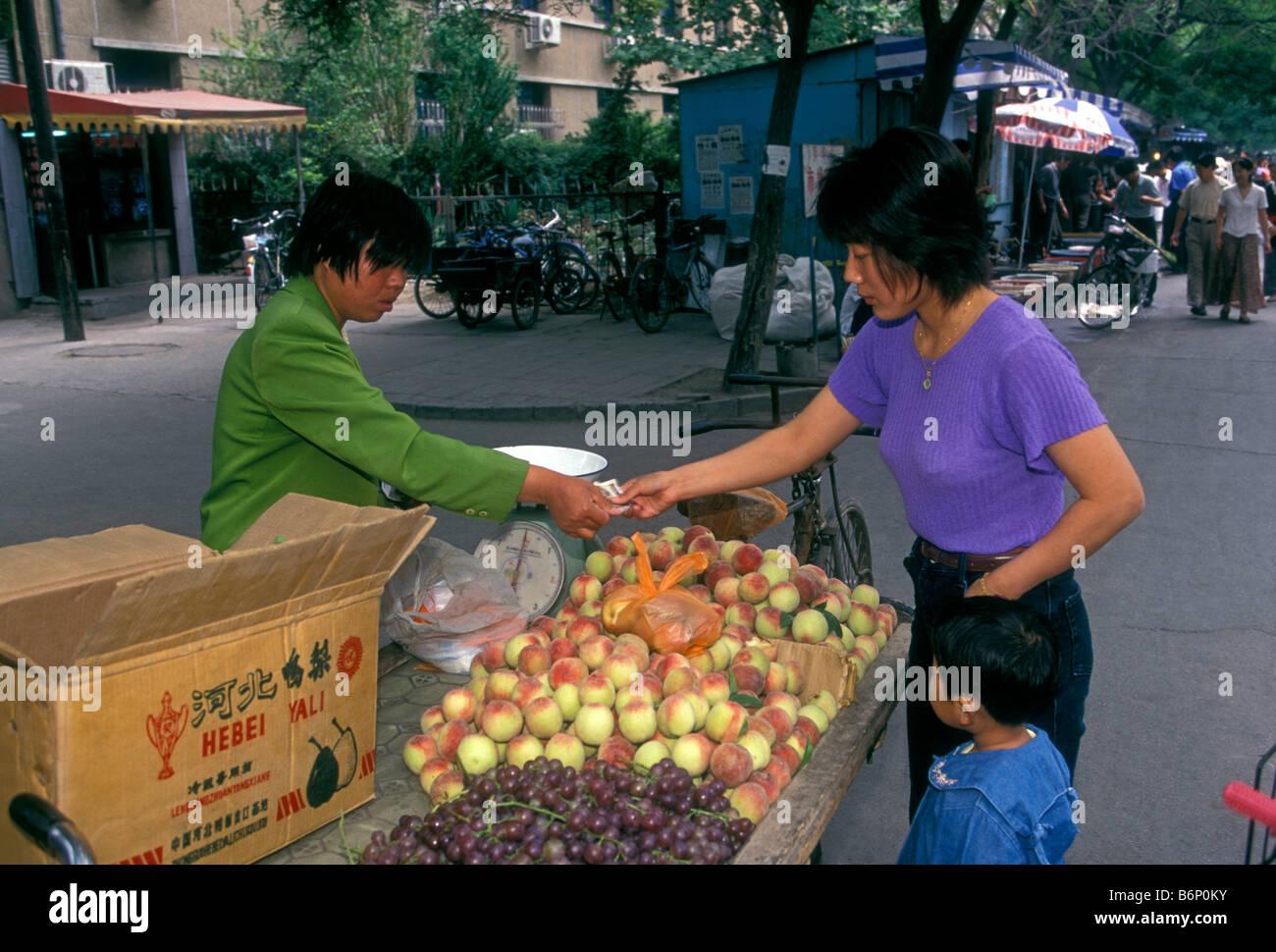 Le donne cinesi, fornitore di frutta, vendita di pesche, pesche fresche, mercati all'aperto, mercato mercato Puhuangyu, Pechino, Municipalità di Pechino, Cina, Asia Foto Stock