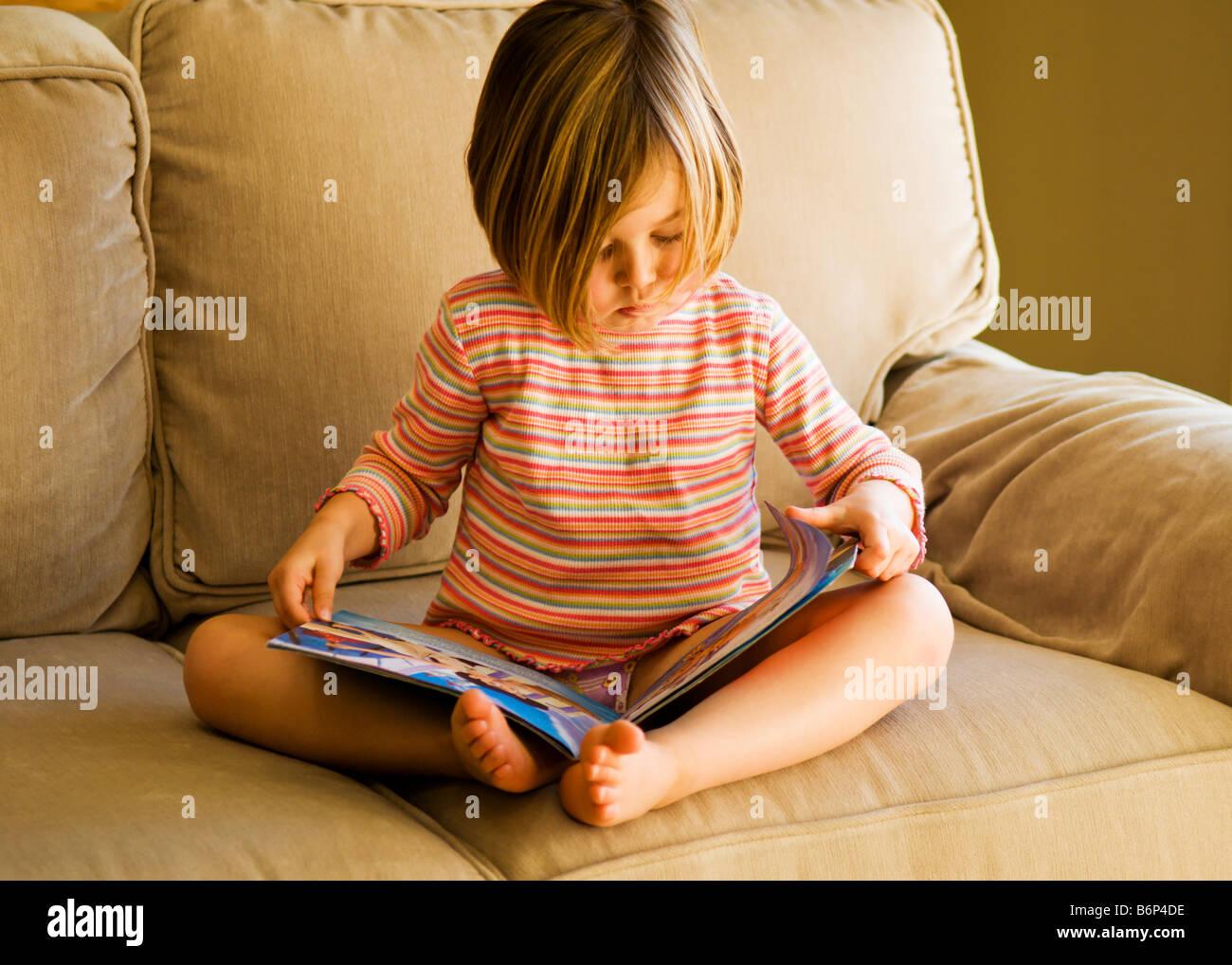 Ragazza, 3-5 anni, si siede su un comodo divano a leggere un libro. Immagini Stock
