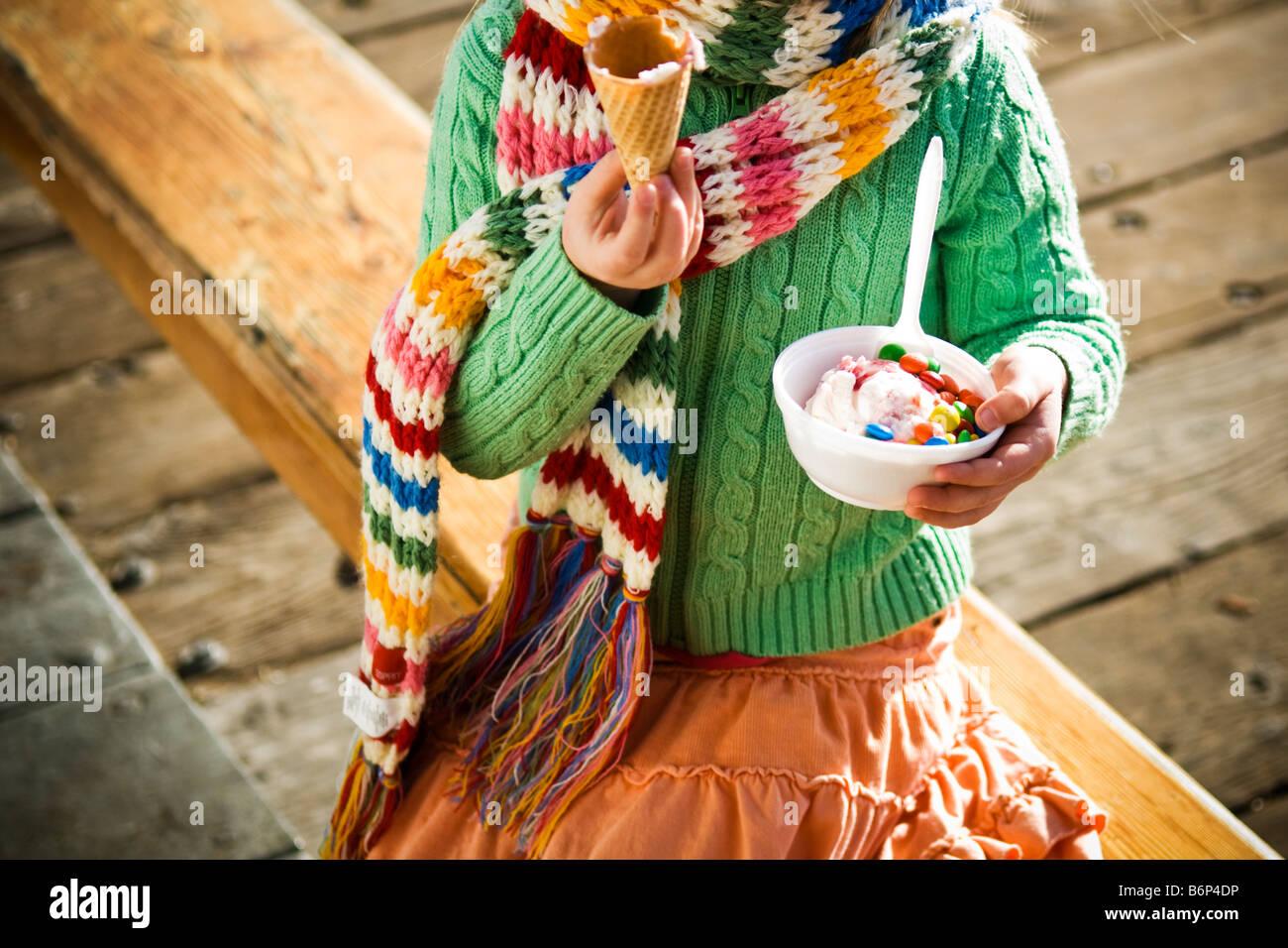 Una ragazza, 4-5 anni, gode di una coppa di gelato e m&m's in una fredda giornata. Foto Stock