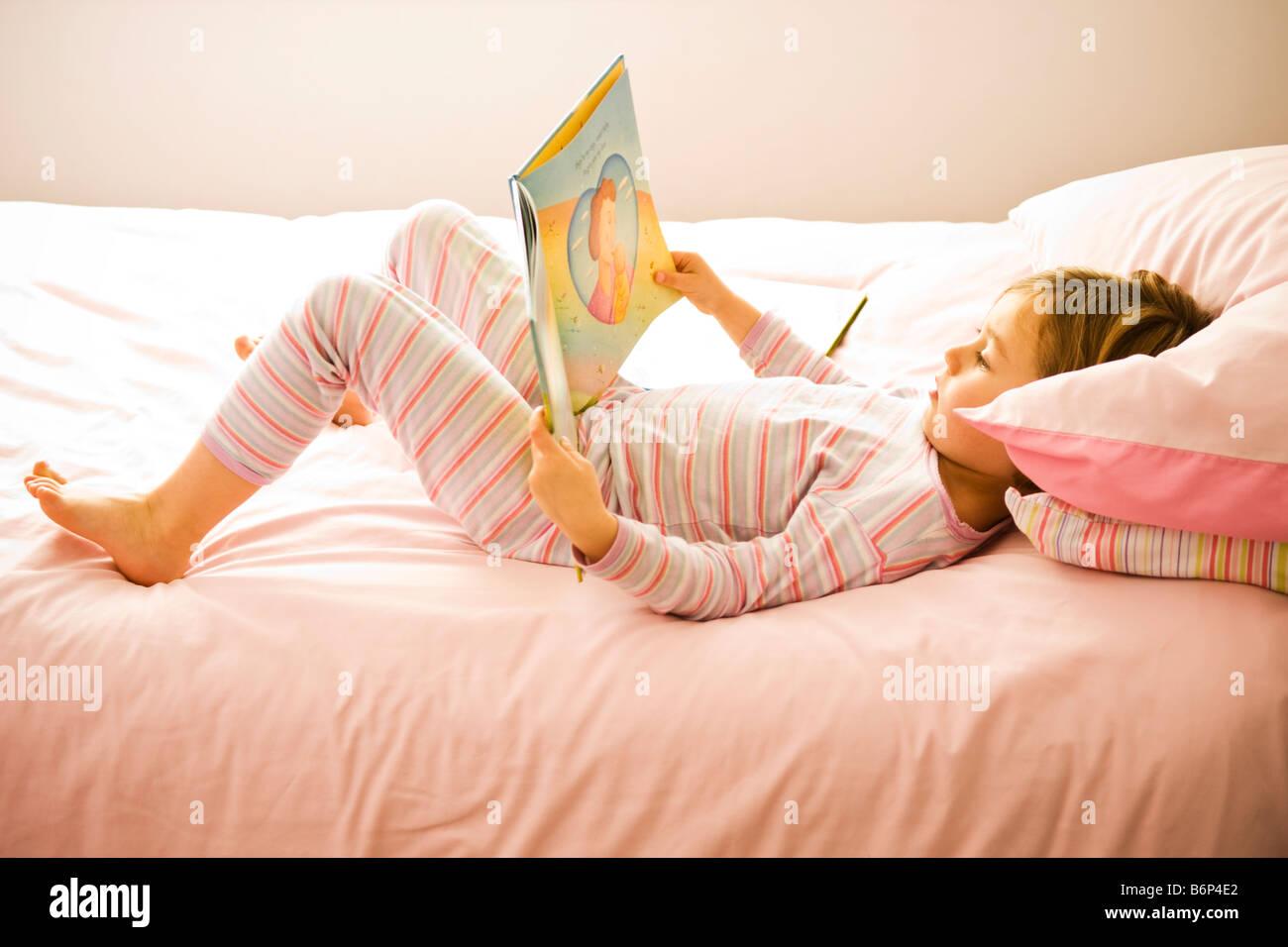 Ragazza, 3-5 anni, giace su un confortevole letto rosa la lettura di un libro. Immagini Stock