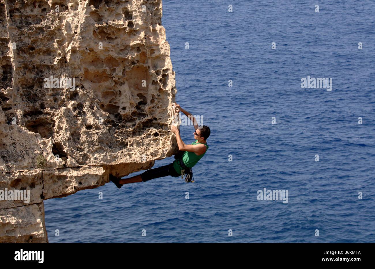 Un rocciatore appeso fuori da una formazione rocciosa al di sopra del mare durante una salita in Gozo, isola sorella Immagini Stock