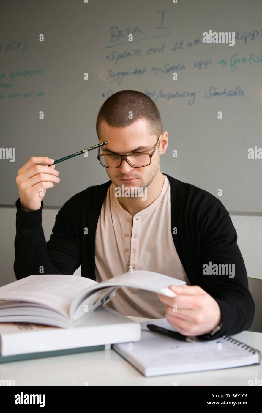 Guy concentrandosi sui suoi studi Immagini Stock