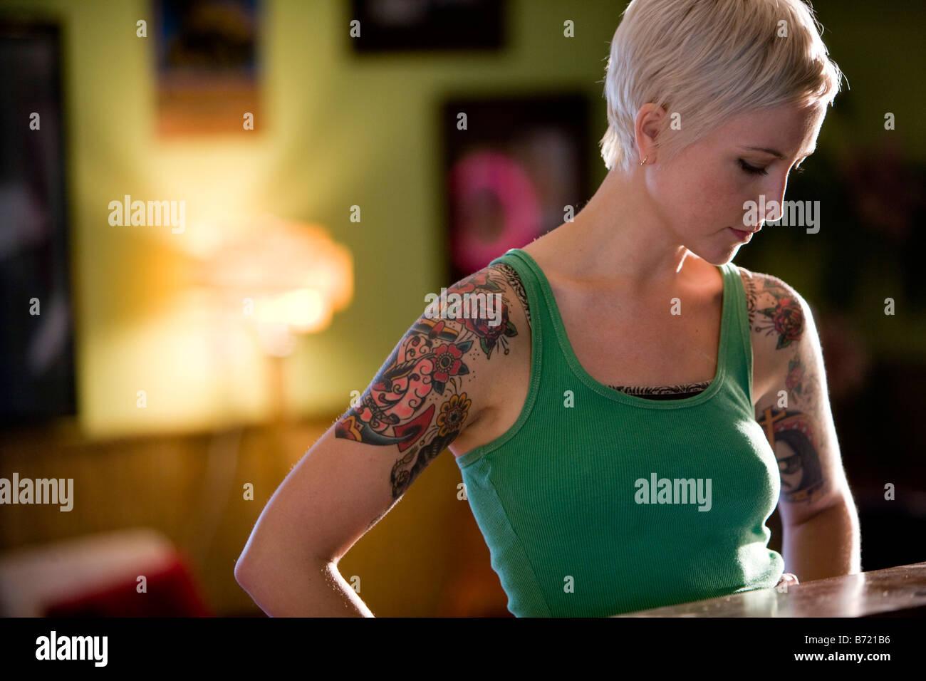 Giovane donna con il design del tatuaggio sul braccio guardando verso il  basso 889f47c4a704