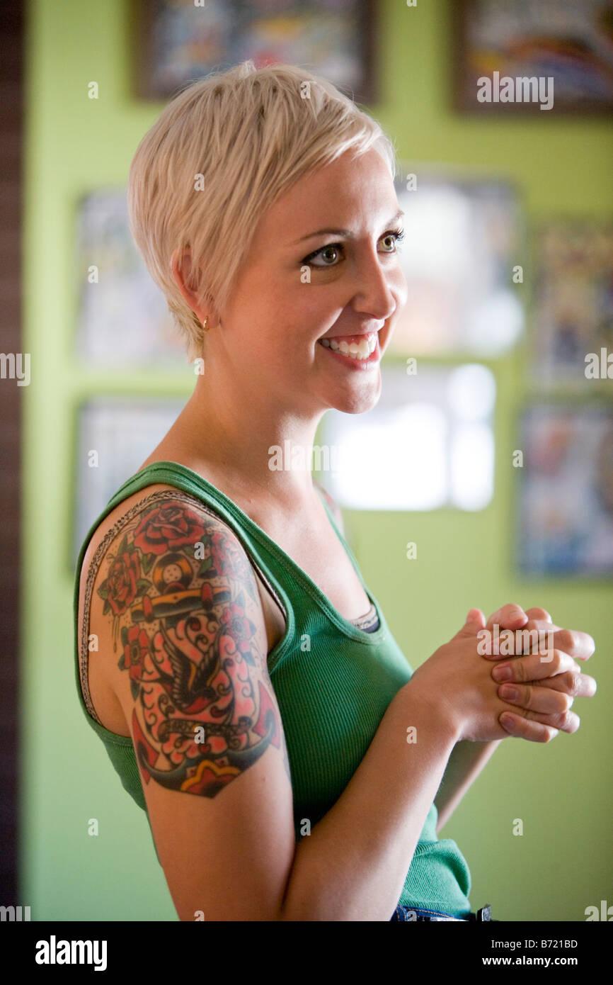 Vista laterale del sorridente giovane donna con il tatuaggio sul braccio 727158c7ac96