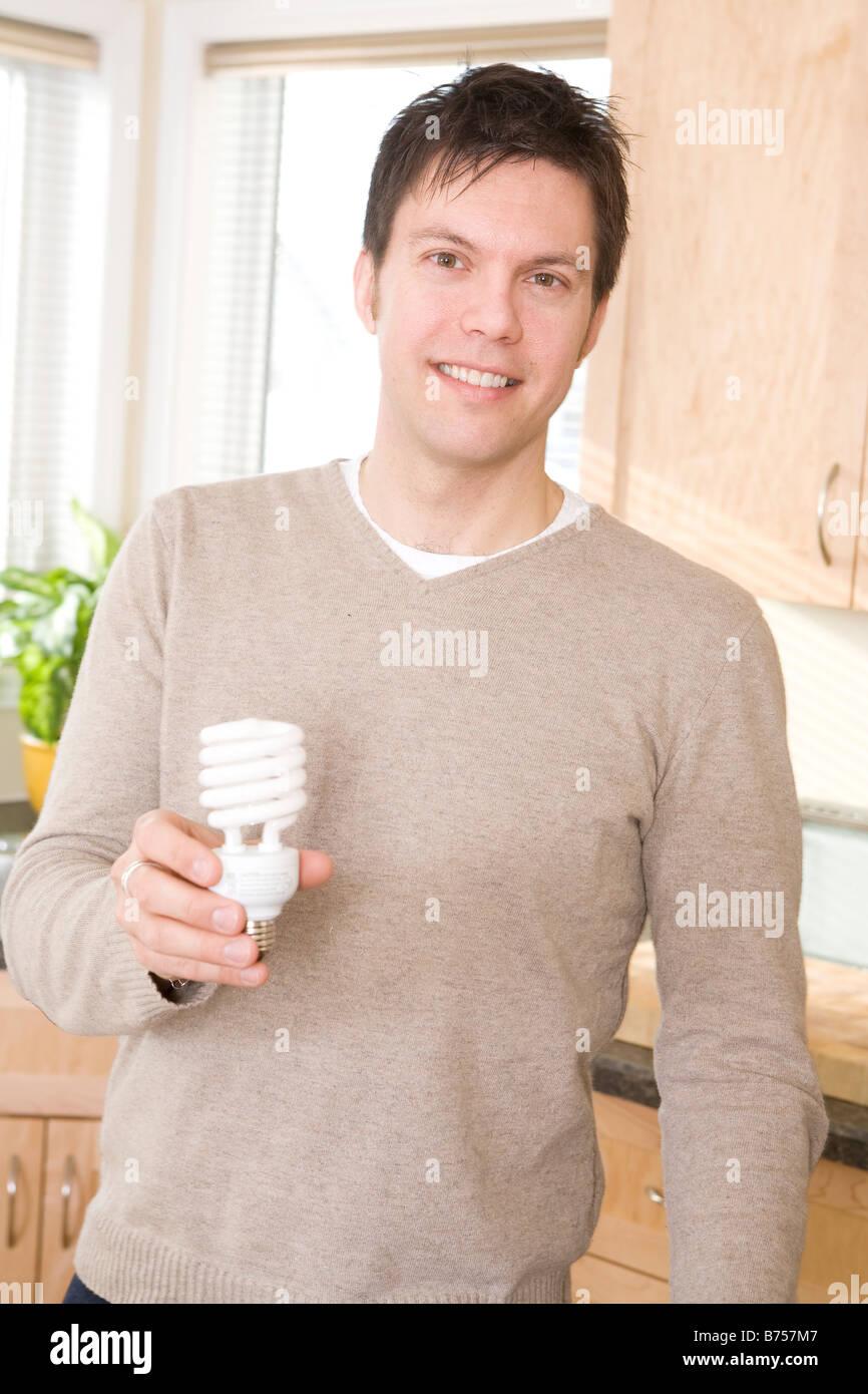 L'uomo azienda efficiente di energia fluorescente compatta lampadina, Winnipeg, Canada Immagini Stock