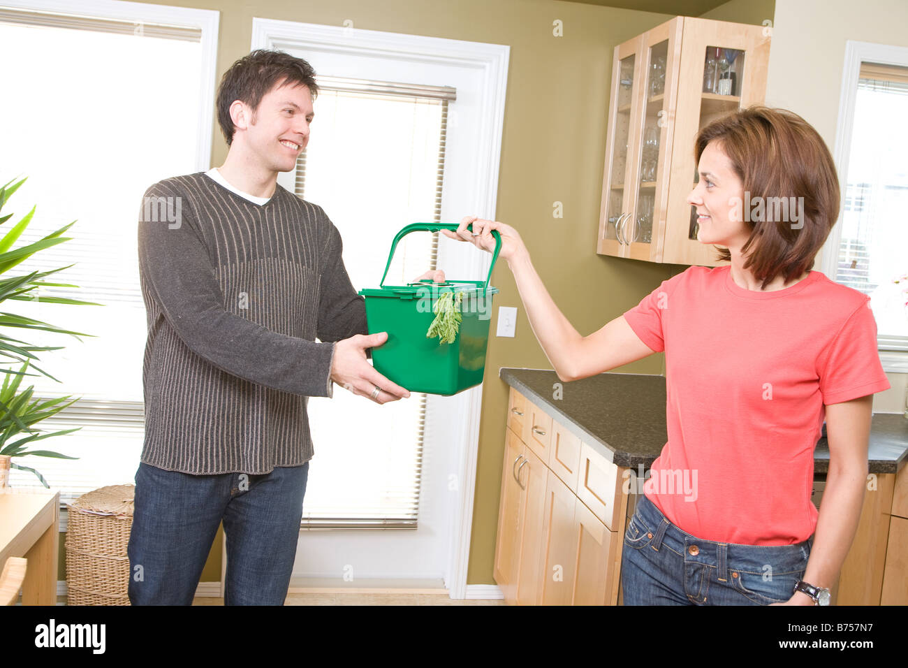 Donna mani cucina compost bin per l'uomo, Winnipeg, Canada Immagini Stock
