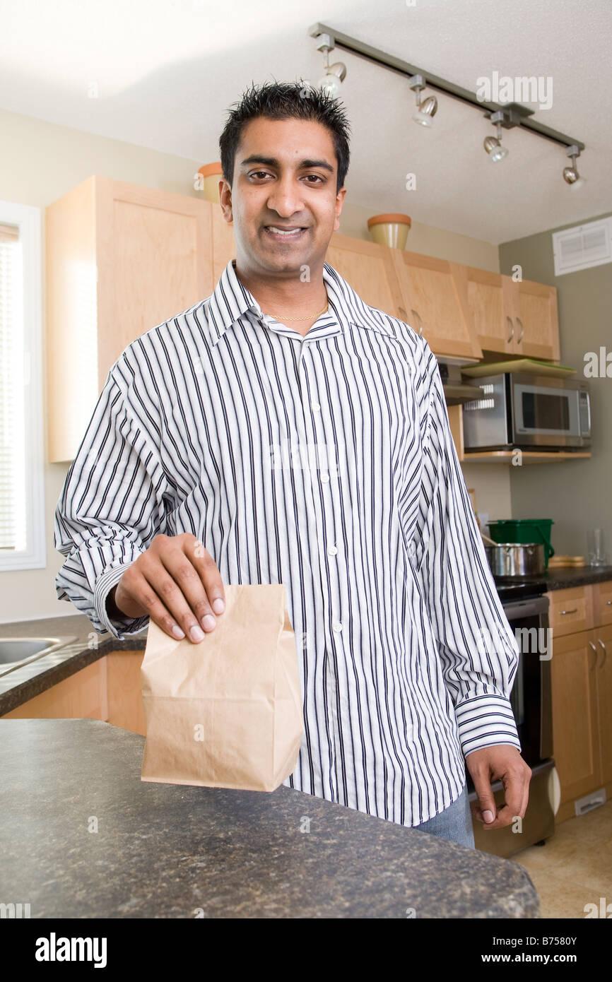 Uomo in cucina accanto al cestino pranzo, Winnipeg, Canada Immagini Stock