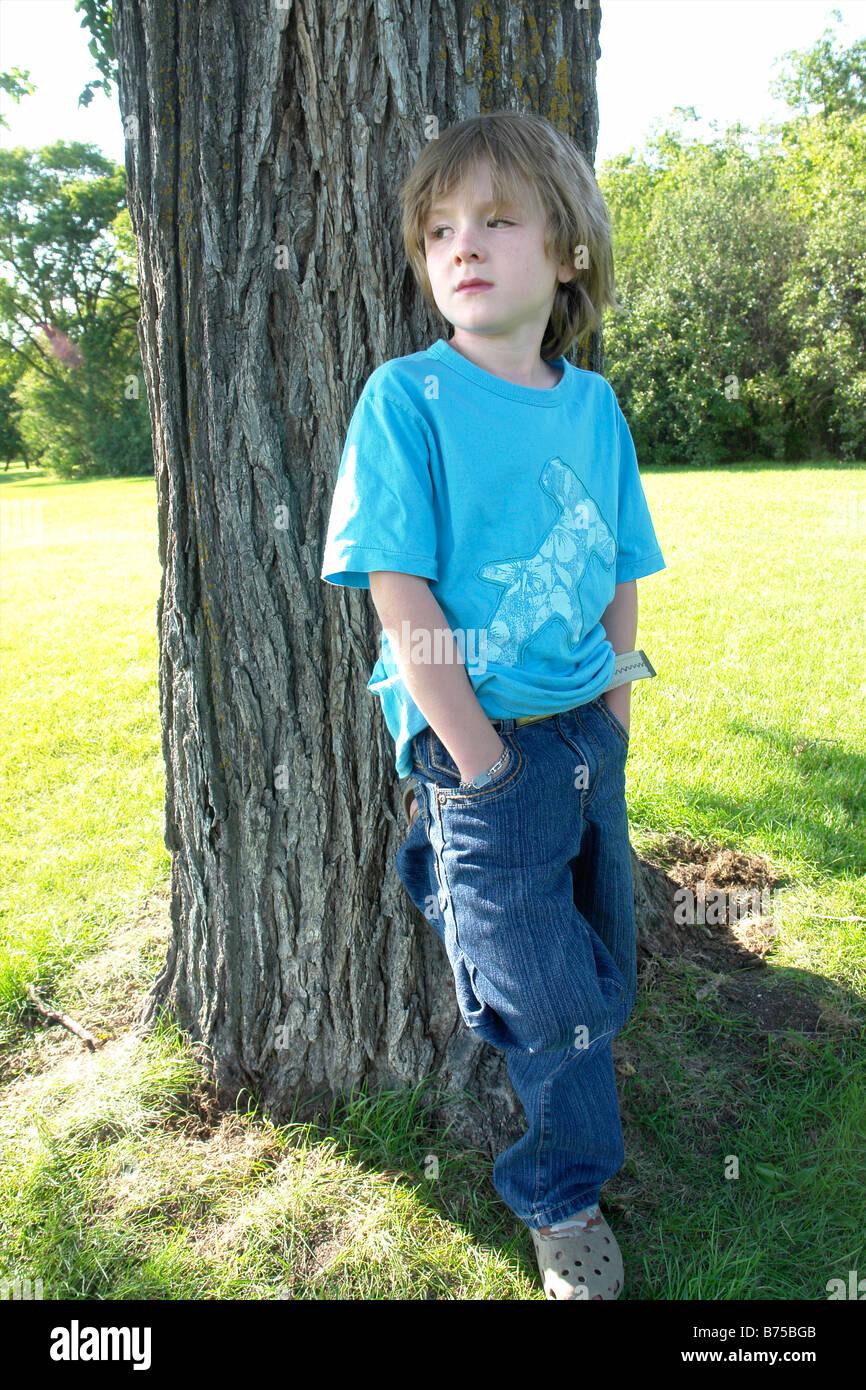 6 anno vecchio ragazzo con le mani nelle tasche al fianco di albero, Winnipeg, Canada Immagini Stock