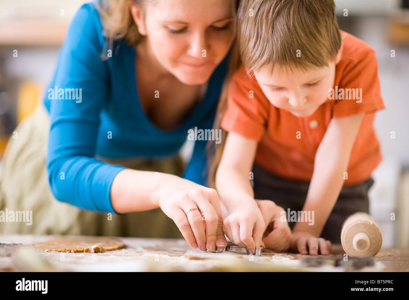 Giovane madre e figlio in cucina rendendo i cookie Immagini Stock