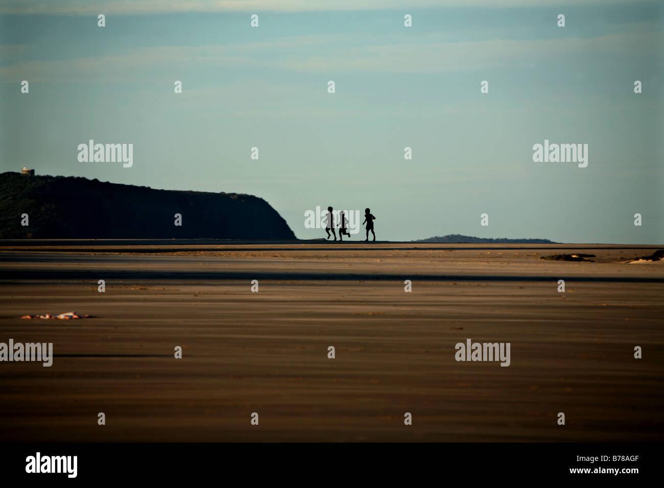 Tre bambini giocano sulla spiaggia al tramonto vicino a Crescent capi Australia Immagini Stock
