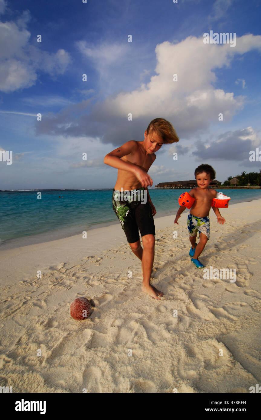 I bambini che giocano a calcio sulla spiaggia della Laguna Resort, Maldive, Oceano Indiano Immagini Stock