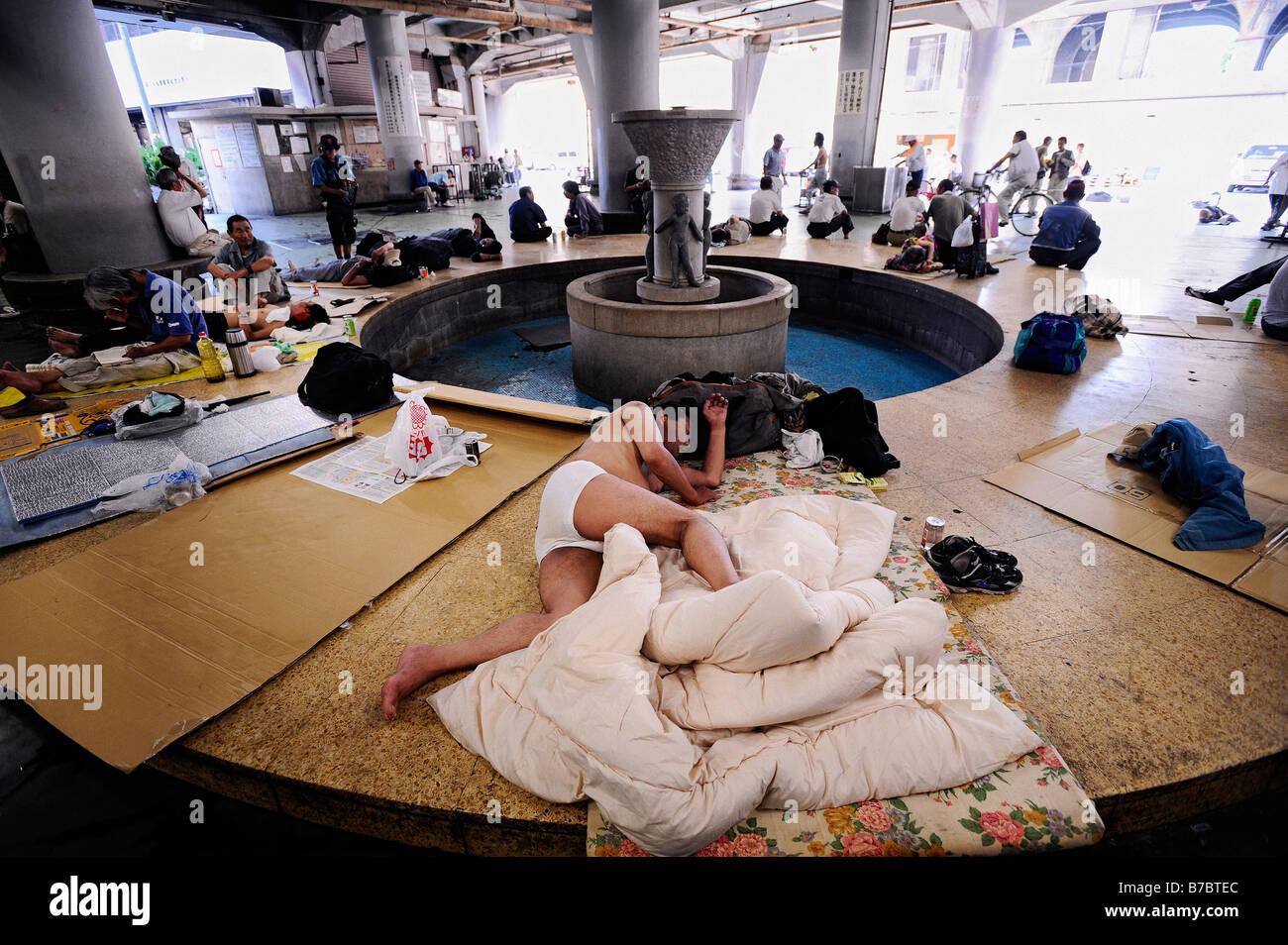 Senzatetto e disoccupati uomini appendere intorno ad una zona comunale della manodopera Nishinari centro benessere Immagini Stock