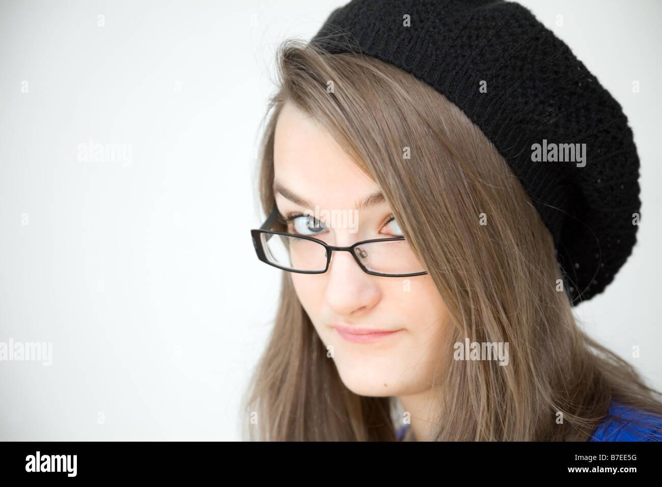 Clever teenage girl teen indossando un cappello e dare un occhiata di traverso sopra gli occhiali, REGNO UNITO Immagini Stock