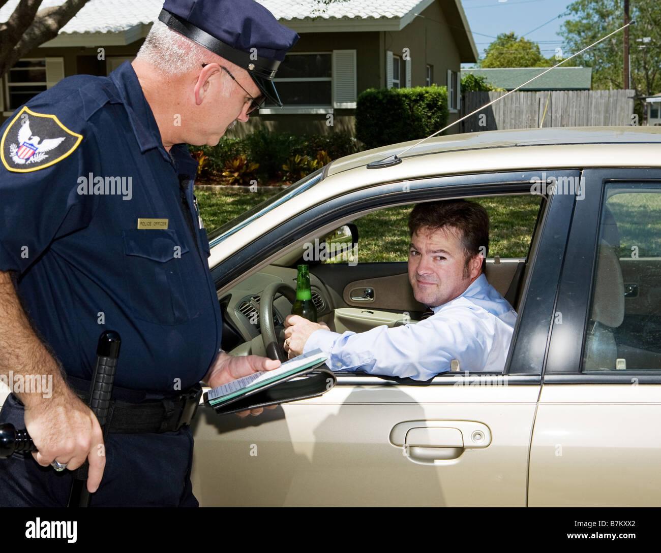 Funzionario di polizia tirando su un autista ubriaco il conducente è in possesso di una birra e guardando imbarazzato Immagini Stock