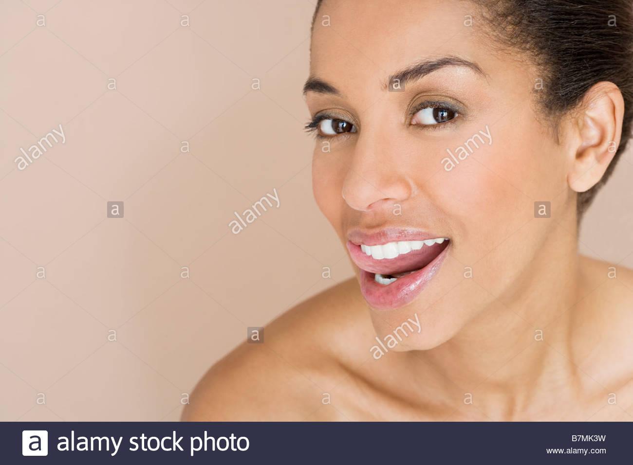 Una donna in esecuzione linguetta lungo i suoi denti Immagini Stock